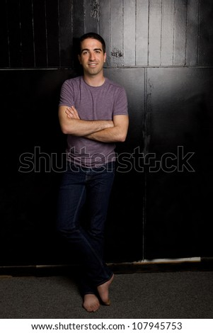 Good looking young guy leaning against black wall looking at camera
