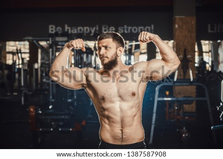 Good looking young man bodybuilder posing in front of the mirror shows big biceps at the gym darkened slogan background. Athlete showing straining veins on hands bubble guts.