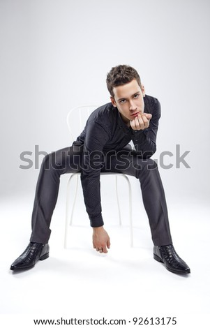 good looking young man sit at chair in studio