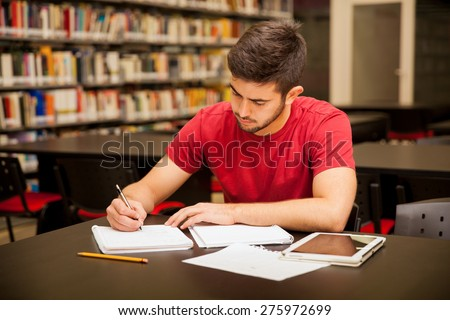 Good looking young man taking some notes and doing school work in a library