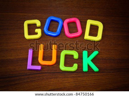 Good luck in colorful toy letters on wood background - stock photo