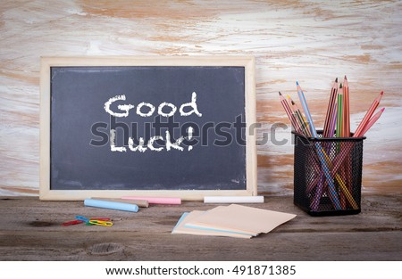 Good luck text on a blackboard. Old wooden table with texture #491871385