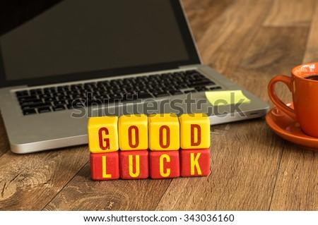Good Luck written on a wooden cube in a office desk #343036160