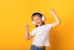 Good Mood. Adorable asian kid listening to music wearing wireless headset and dancing, isolated over yellow wall