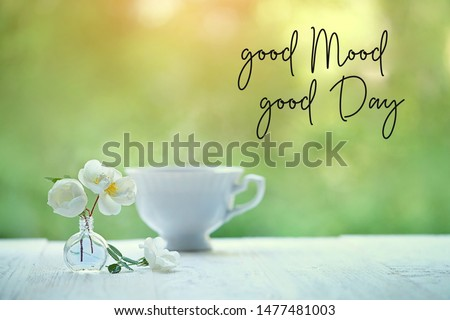 good mood, good day - inspiration motivation quote. beautiful gentle spring or summer still life with Cup of tea and  wild rose flowers on abstract green natural background. romantic breakfast