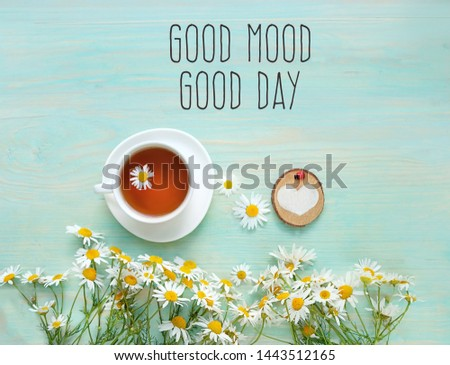 Good Mood, good day - inspiration quote. beautiful composition with chamomile flowers and cup of tea on table. mint color Rustic background with daisies flowers, tea and heart. breakfast, tea ceremony