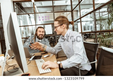 Good mood. Nice smart man smiling to his colleague while being in a good mood