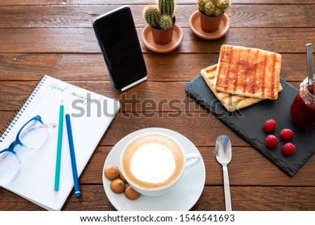 Good morning breakfast. Wooden rustic table with a homemade cappuccino and homemade marmelade. Message on paper. Cellphone and plants