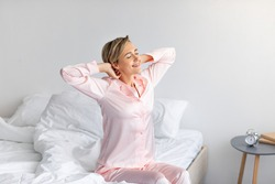 Good Morning. Cheerful positive middle-aged lady stretching arms and back after waking up, happy female in pink silk sleepwear sitting on bed, feeling great, enjoying good start of the day, free space