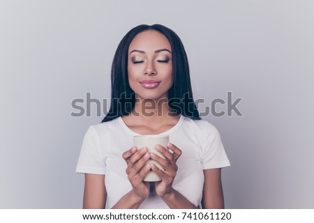 Good morning! Close up portrait of charming dreamy african young woman, drinking hot tea. She is relaxed, in casual white wear, with closed eyes