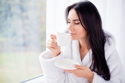 Good morning! Close up portrait of charming dreamy brunette young girl drinking coffee. She is sleepy and relaxed