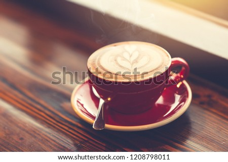 good morning coffee at windows on wooden table with latte art vintage color tone.