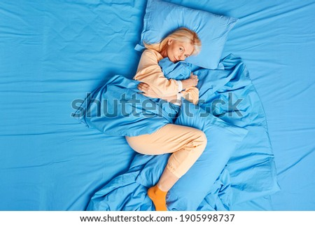 Good morning concept. Satisfied forty years old European woman feels relaxed awakes early enjoys new day wears casual pajama embraces soft blanket rests long during day off. View from above. Stock photo ©