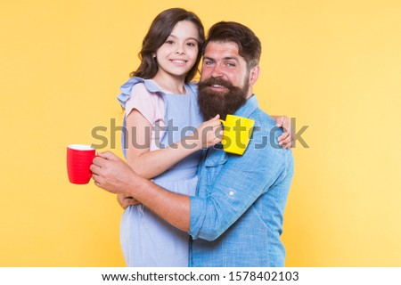 Good morning. Having coffee together. Healthy lifestyle. Family drinking tea. Bearded man and happy girl holding mugs. Father and daughter hot drink. Drink water. Drink fresh juice. Breakfast concept.