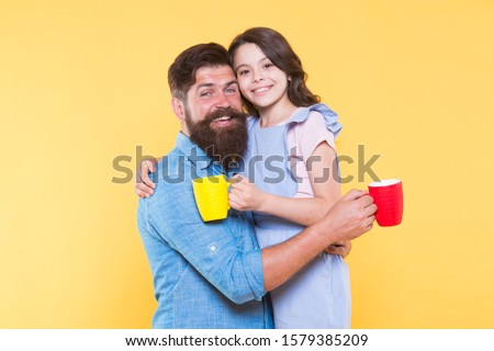 Good morning. Having coffee together. Lovely family tradition. Drinking tea. Bearded man and happy girl holding mugs. Father and daughter hot drink. Drink water. Drink fresh juice. Breakfast concept.