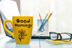 Good morning message on coffee cup at workplace background