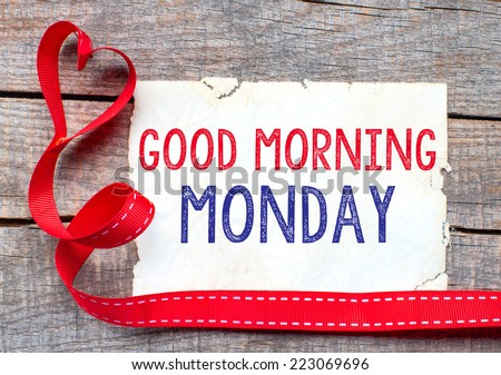Good Morning Monday. White card with text Good Morning Monday on wooden table, with red ribbon