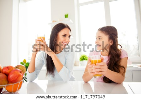 Good morning! Nice attractive beautiful caucasian mummy smiling at her small little offspring daughter, wearing casual, drinking orange juice in light kitchen #1171797049