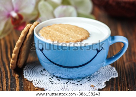 Good morning or Have a nice day message concept - bright blue cup of milk with cookies. Cup of milk with smile. Health and diet concept on the wooden table, close up.
