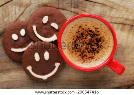 Good morning or Have a nice day message concept - bright red cup of frothy coffee with smiling chocolate cookies