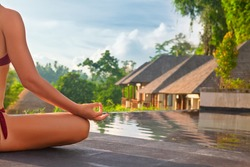 Good morning with yoga meditating on sunrise background. Active woman in bikini practicing on villa poolside to keep fit and health. Woman fitness training, sport activity on summer family holiday.