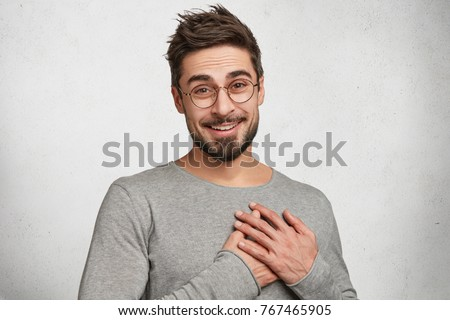 Good natured attractive young stylish hipster guy has friendly expression, keeps hands on heart, expresses his feelings to girlfriends, shows love and great sympathy, isolated over concrete white wall #767465905