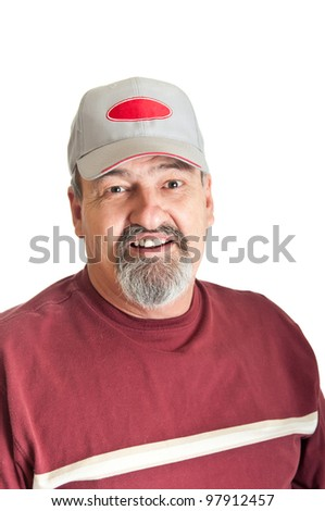 Good natured smile from a sixty five year old man wearing a baseball cap. isolated on a white background.