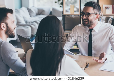 Good news for you! Happy young loving couple bonding to each other and looking at man sitting in front of them at the desk and gesturing