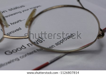 Good news. Your content has been approved. Word Approved magnified by glasses lens. Printout of email from a stock photo agency