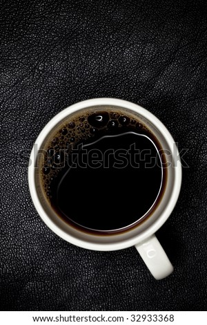 good night espresso coffee in white cup top view, black leather backdrop, shallow DOF