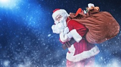 Good old Santa Claus carries a big heavy bag with gifts under the snow. Magic Christmas night.