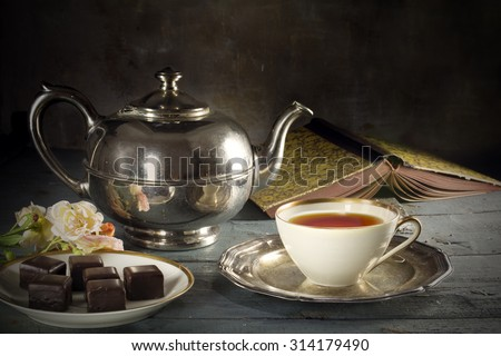 good old tea time, black tea in a porcelain cup, old-fashioned silver teapot, chocolate cookies and a good book on a rustic wooden table, copy space in the dark brown background