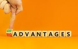 Good or bad advantages symbol. Businessman turns a wooden cube, changes words bad advantages to good advantages. Beautiful orange background, copy space. Business, good or bad advantages concept.