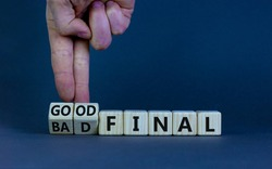 Good or bad final symbol. Businessman turns wooden cubes and changes words 'bad final' to 'good final'. Beautiful grey table, grey background, copy space. Business and good or bad final concept.
