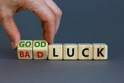 Good or bad luck symbol. Businessman turns wooden cubes and changes words 'bad luck' to 'good luck'. Beautiful grey background, copy space. Business and good or bad luck concept.