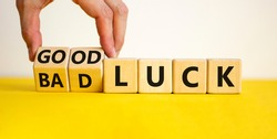 Good or bad luck symbol. Businessman turns wooden cubes and changes words 'bad luck' to 'good luck'. Beautiful yellow table, white background, copy space. Business and good or bad luck concept.