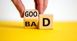 Good or bad symbol. Businessman hand turns a cube and changes the word 'bad' to 'good'. Beautiful yellow table, white background, copy space. Business and bad or good concept.