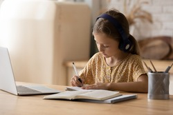 Good pupil. Little girl get remote distant education online listen to teacher tutor at virtual class lesson take write notes by hand. Schoolchild in headphones use modern tech in learning by internet