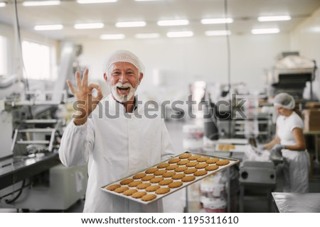 Good quality.Picture of mature cheerful male employee in sterile clothes standing in bright food factory . Holding tray full with fresh cookies and gesturing with his hand that quality is good.