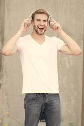 Good sound for happy experience. Happy man listen to music grey background. Handsome guy enjoy happy melody playing in headphones. Pleasure and joy. Fun and entertainment. Be happy and positive