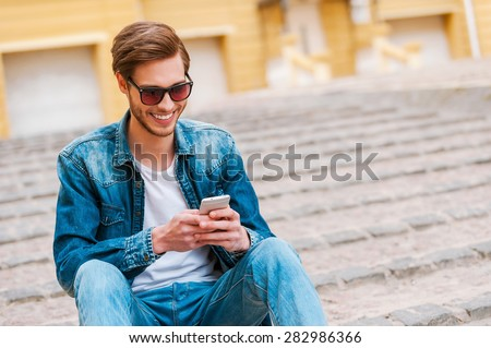 Good spending time in his city. Confident young man holding mobile phone while sitting outdoors stock photo