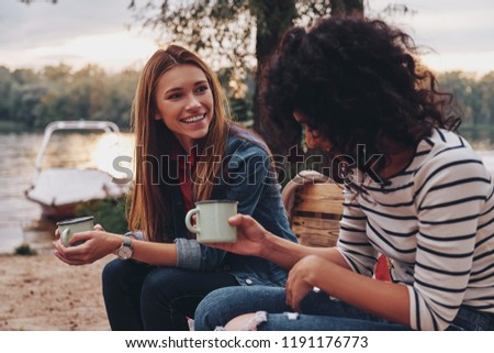 Good talk with friend. Two young beautiful women in casual wear smiling and talking while enjoying camping near the lake Stock photo ©