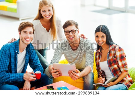 Good team is a key to success. Group of happy young people working together while sitting in the rest area of their office