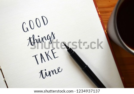 GOOD THINGS TAKE TIME written in notepad on desk with cup of coffee #1234937137