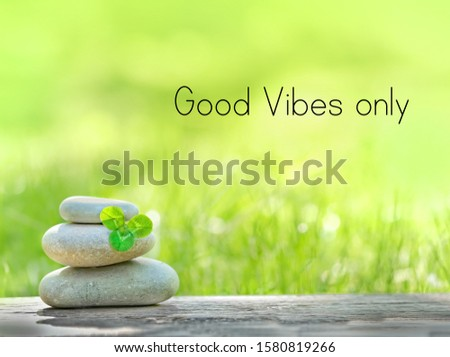 good vibes only - motivation quote. Stack of zen stones and Shamrock clover leaf on nature background. Relax, spa wellness scene, soul calmness concept.