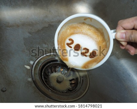 Goodbye 2020, a year that many want time to flies by. Holidays food art theme hand holding and pouring coffee with number 2020 on frothy surface from white cup over dirty stainless steel kitchen sink.