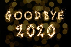 Goodbye 2020. Bright text made of sparkler on black background with blurred lights