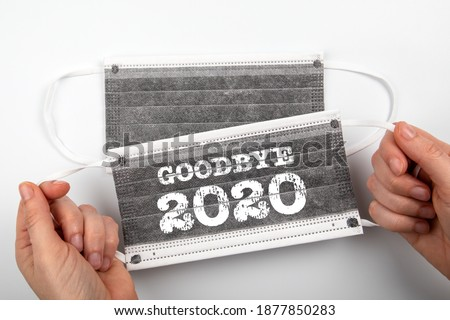 Goodbye 2020. Business, education, health and review concept. Two face masks on a white background