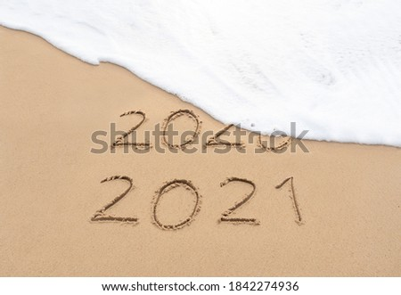 Goodbye 2020 Happy New Year 2021 sign on sandy beach with foam wave. Handwritten 2020 and 2021 on beautiful sand beach. New Years 2021 replace 2020 concept