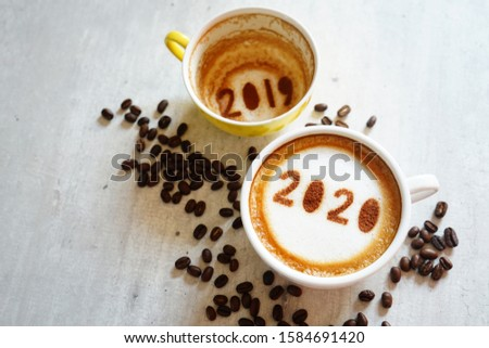 Goodbye 2019 Hello 2020 holidays food art theme coffee cup with number 2020 on frothy surface, another one with 2019 at the bottom of cup over grey cement background with coffee beans / space for text